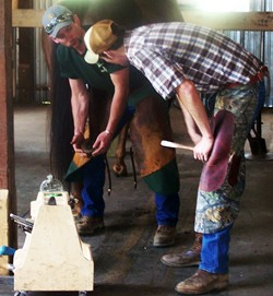 John Crothers works with a student at Meredith Manor's Horseshoeing School
