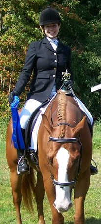 A student receives a blue ribbon in a horse showing class at Meredith Manor.